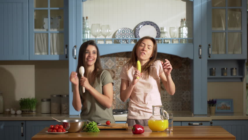 Portrait of two energetic young women dancing and singing, while cooking salat at kitchen with fresh vegetables