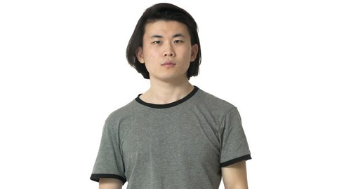 Portrait of concentrated chinese man in casual gray t-shirt touching his chin and thinking or remembering important things, isolated over white background. Concept of emotions