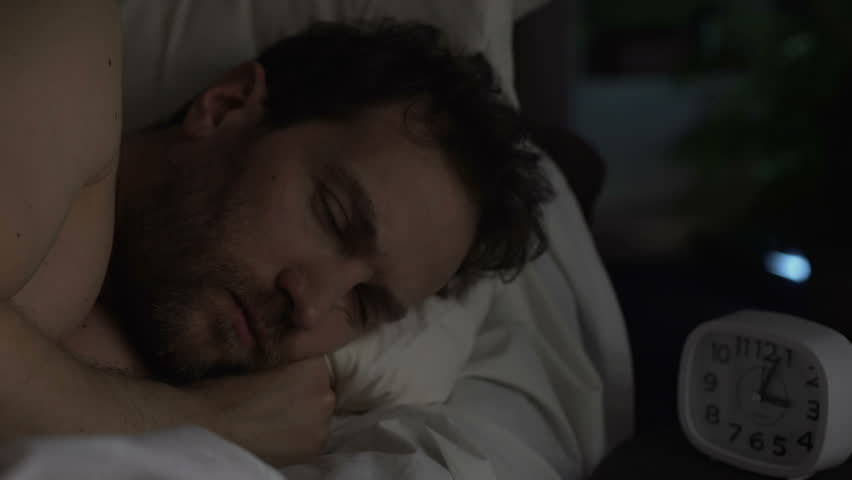 Man in his 40s suffering insomnia, turning in bed and looking angrily at clock | Shutterstock HD Video #1009165880