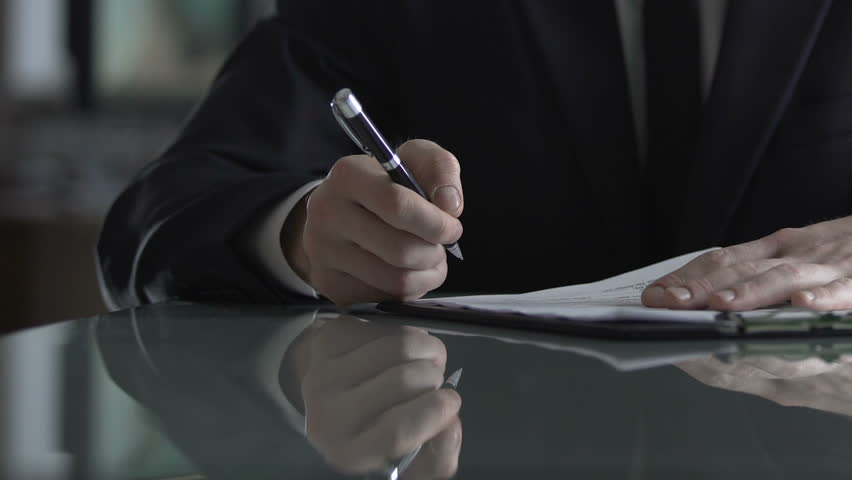 Businessman signing contract after successful negotiation, deal acceptance