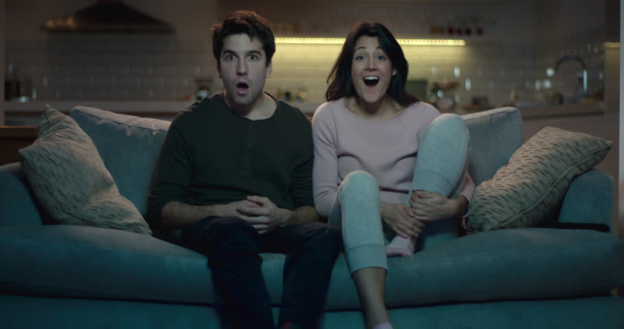 Man and woman watching tv with shocked expressions on their faces.