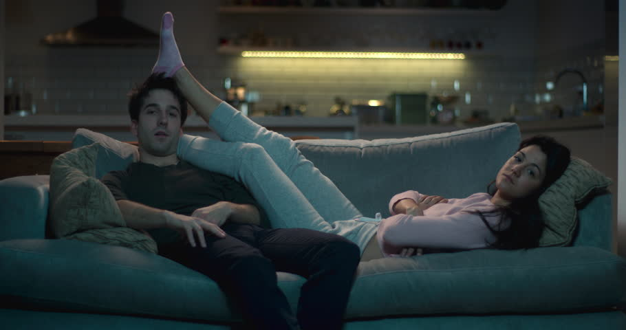 Man and woman slumped in front of the tv.