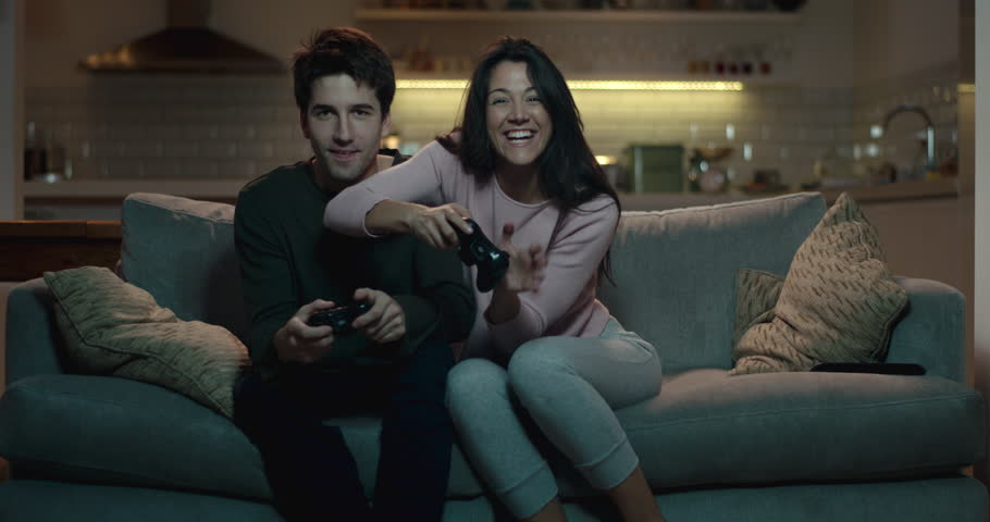 Competitive couple push and shove each other as they play a video game at home #1009173398