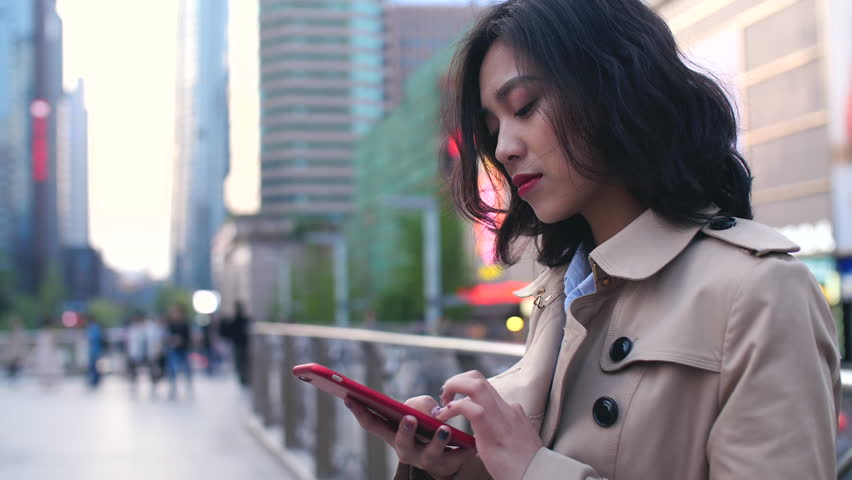 Pretty happy young asian woman using mobile phone in the Chinese city of Chengdu at afternoon on the overpass with busy street in the background | Shutterstock HD Video #1009177616