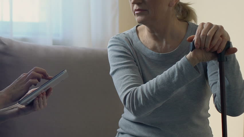 Doctor keeping electronic medical record in tablet, examining old woman at home | Shutterstock HD Video #1009182182