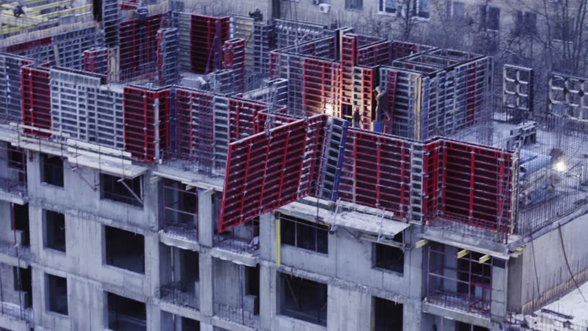 Workers on the top of the building under construction at the evening in winter. They are making formwork | Shutterstock HD Video #1009193429