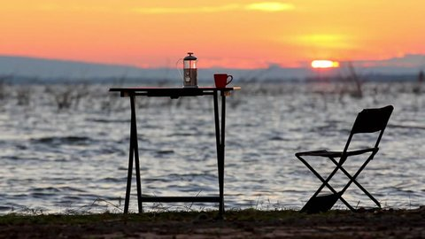 cup of coffee on the table beside the lake with sunrise background