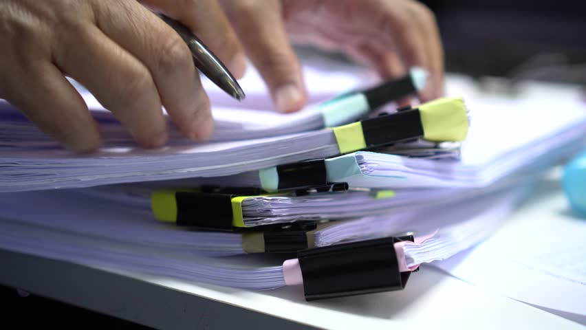 Businessman searching documents files or information in Stack of papers folder on work in office, Business report paper or piles of unfinished document achieves with clips on offices, Business concept | Shutterstock HD Video #1009199438