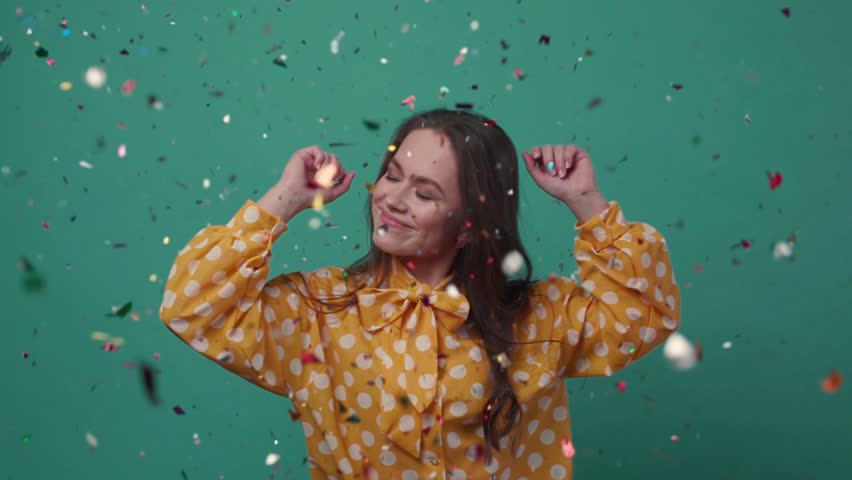 Beautiful young woman dances alone in colorful confetti on a green background.  Royalty-Free Stock Footage #1009206731