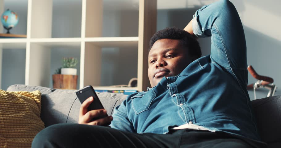 Bored young african american man use phone lazy sit on sofa in home online relax work cell phone app authentic bills sunset guy close up mobile smartphone slow motion portrait handsome rude #1009210196
