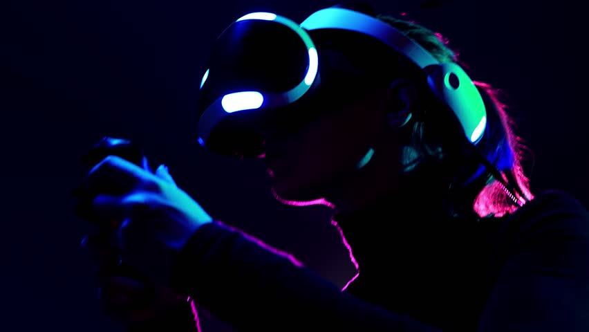 Young woman in VR headset using gamepad have fun and play interactive video game. Virtual reality helmet on black background | Shutterstock HD Video #1009215566