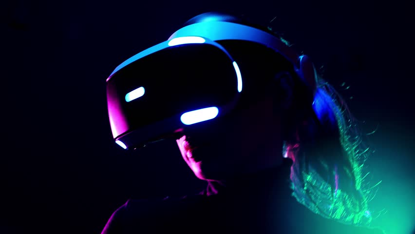Young woman in VR headset using gamepad have fun and play interactive video game. Virtual reality helmet on black background #1009215569