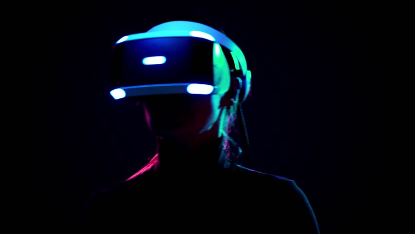 Young woman in VR headset have fun and play interactive game. Virtual reality helmet on black background #1009215575