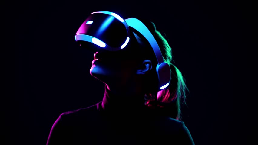 Young woman in VR headset looks around and wonders how amazing. Virtual reality helmet on black background #1009215587