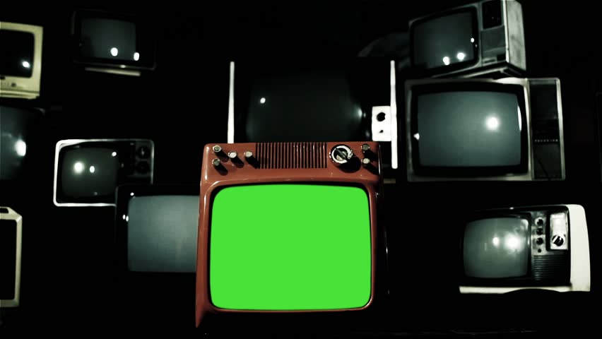 "A Vintage Red TV with Green Screen Around Many Retro TVs. Dolly Shot. Iron Tone. You can replace green screen with the footage or picture you want with ""Keying"" effect in After Effects.  