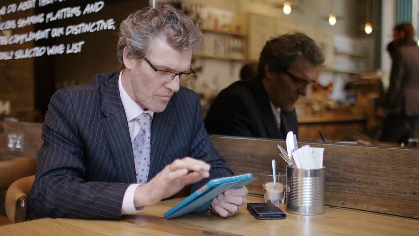 Mature business man using a digital tablet in a coffee shop | Shutterstock HD Video #1009224029