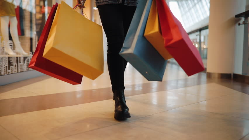 Young blonde woman walks with colorful shopping bags around a shopping mall | Shutterstock HD Video #1009232966
