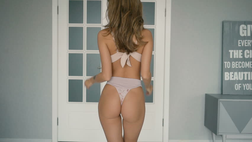 Young seductive girl with long hair perfect sexy body and ass, young woman wearing seductive lingerie, beautiful female in panties posing close to door at home healthy life concept in slow motion