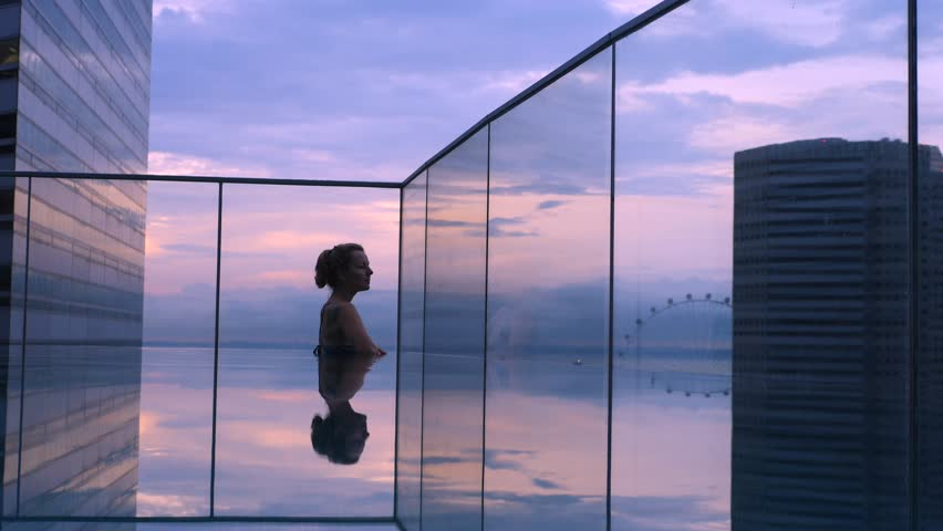 Woman Relaxing In Infinity Swimming Pool In Luxury Hotel At Sunset