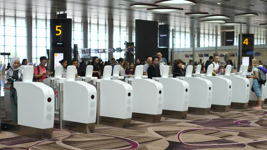 Passengers Passing Through Customs Control With Immigration Automated Clearance System In Airport.