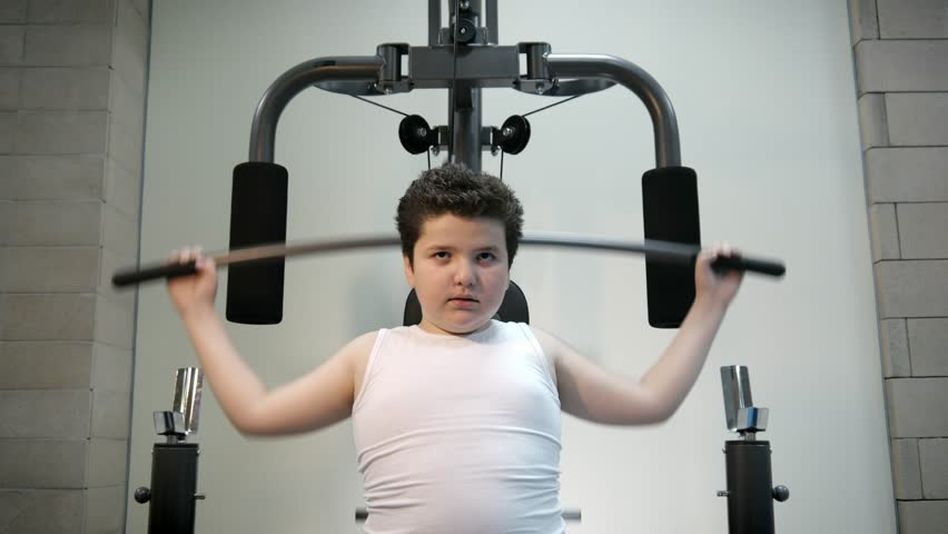 Thick angry kid boy trains in gym fat burning.will power children concept overweight tenacity purpose   Shutterstock HD Video #1009243649