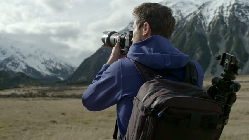 Young adventure photographer taking photographs around Mt Cook, New Zealand. Camera moves around man in slow motion as sun peeks through clouds.