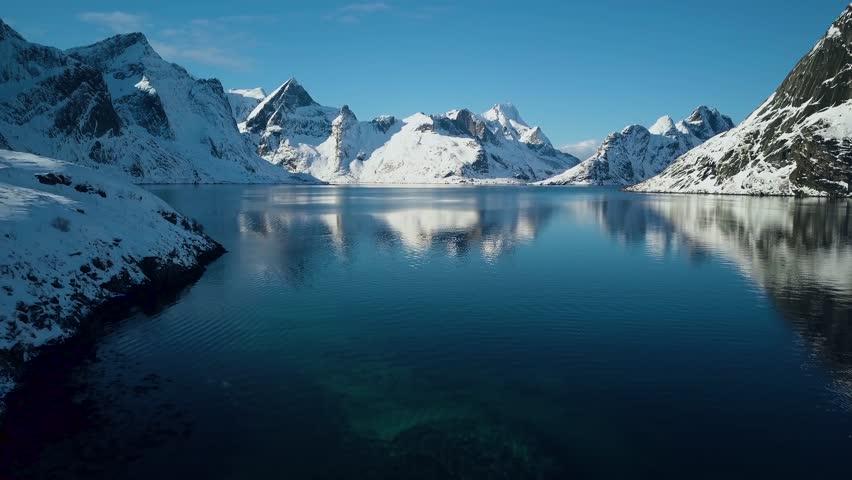 Breathtaking snow covered mountains of Reine, Norway.  Lofoten Islands archipelago in winter.  4k Aerial drone footage