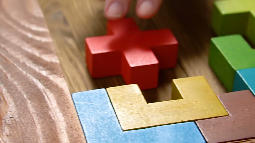 Woman's hand folds colorful wooden blocks on the brown table background, close up, pan shot. The business concept.