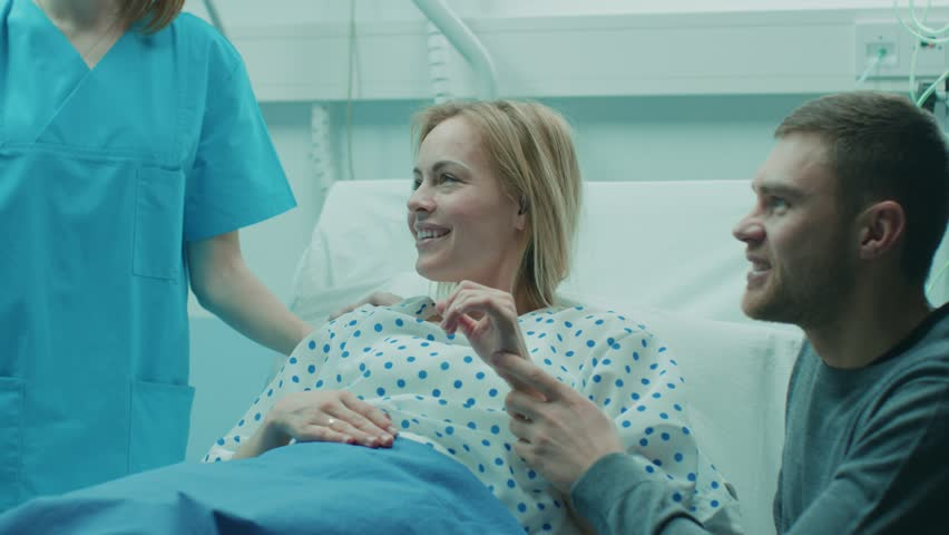 In the Hospital Midwife Gives Newborn Baby to a Mother to Hold, Supportive Father Lovingly Hugging Baby and Wife. Happy Family in the Modern Delivery Ward. Shot on RED EPIC-W 8K Helium Cinema Camera. #1009293641
