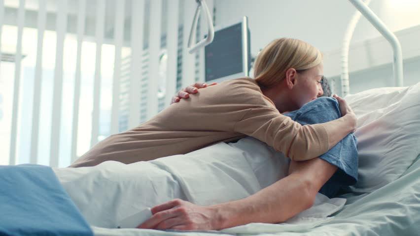 In the Hospital, Happy Wife Visits Her Recovering Husband who is Lying on the Bed. They Lovingly Embrace and Smile. Shot on RED EPIC-W 8K Helium Cinema Camera.