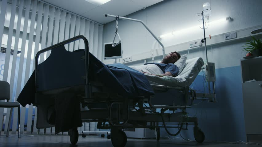 Low Level Shot in the Hospital, Very Sick Man Lying on the Bed, Nurse Checks His Vital Signs and Drop Counter. Shot on RED EPIC-W 8K Helium Cinema Camera.