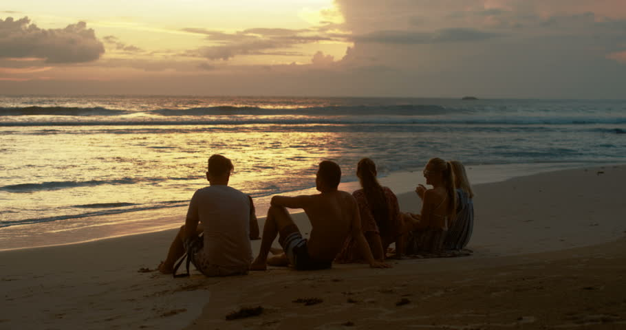 Group of Beautiful Girls and One Man Sitting on the Beach Looking at the Sunset. Romantic Day for Young People Having Fun. Beautiful Nature. Shot on RED Epic 4K UHD Camera.