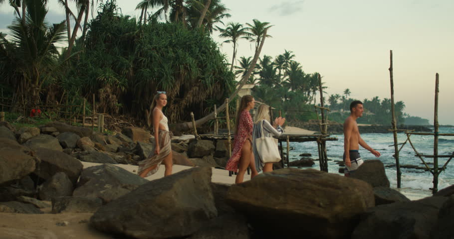 Following Shot of Three Beautiful Girls and One Handsome Man Walking Along the Beach. In the Background Green Forest with Palm Trees, Fishing Stilts and Sea with Waves. Shot on RED Epic 4K UHD Camera.