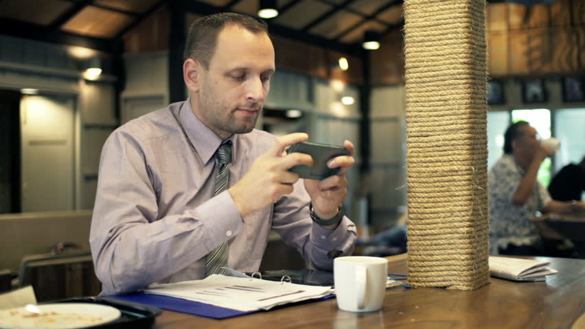 Young businessman playing game on smartphone in cafe  | Shutterstock HD Video #10093208