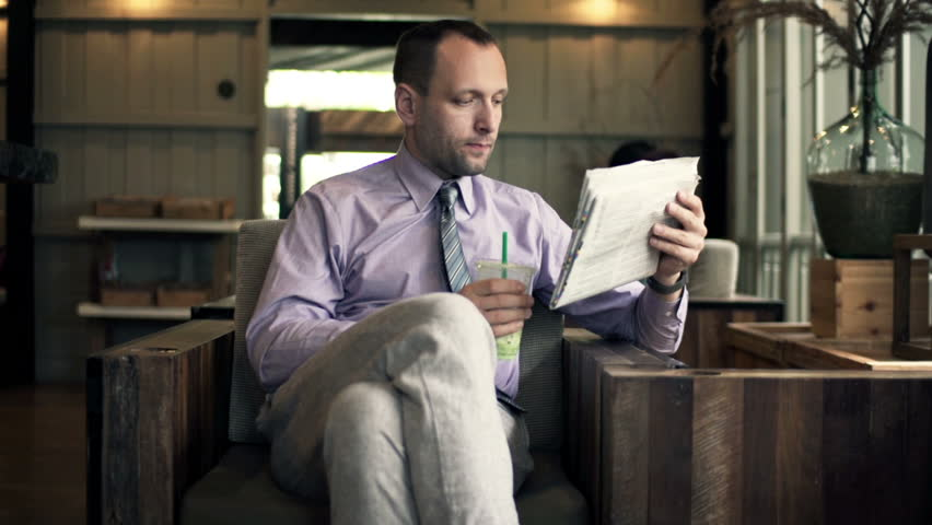 Young businessman reading newspaper and drinking cocktail in cafe  | Shutterstock HD Video #10093265