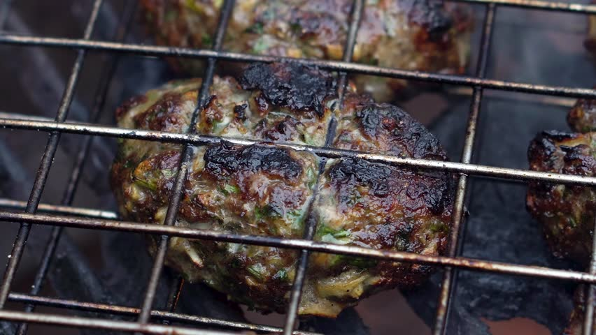 Extreme closeup of a single kofta cooking on a hot grill with smoke and flames.   Shutterstock HD Video #1009333625