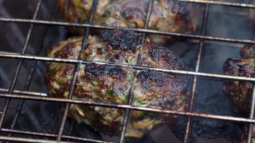 Zoom out from extreme closeup to wide shot of kofta on a hot grill with smoke and flames. | Shutterstock HD Video #1009335062