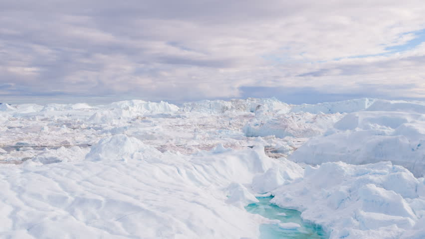 Global Warming and Climate Change - Icebergs and ice from melting glacier in icefjord in Ilulissat, Greenland. Aerial video of arctic nature ice landscape. Unesco World Heritage Site.