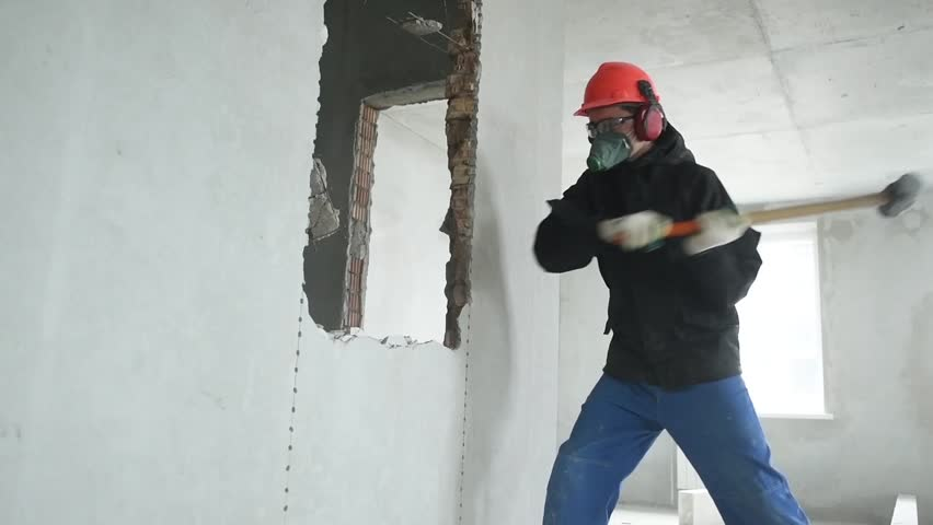 Demolition work and rearrangement. worker with sledgehammer at wall destroying