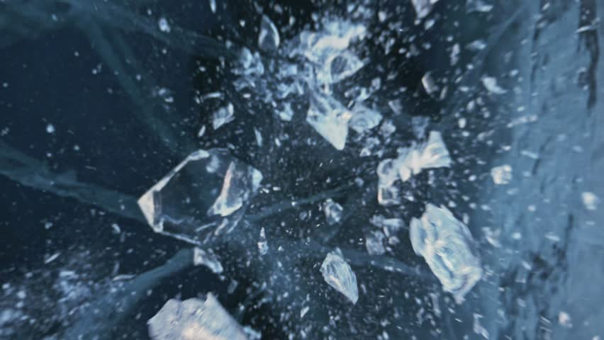 Man in the mittens smashes the ice on the ice. Slow motion. The camera moves behind the ice. A piece of ice is very beautifully broken about the icy with magical cracks. In the frame, a lot of | Shutterstock HD Video #1009349057