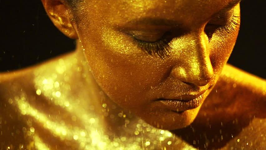 High Fashion model woman in golden bright sparkles posing in studio, portrait of beautiful sexy girl, trendy glowing gold skin make-up. Art design make up. Glitter metallic shine makeup 4K slow motion