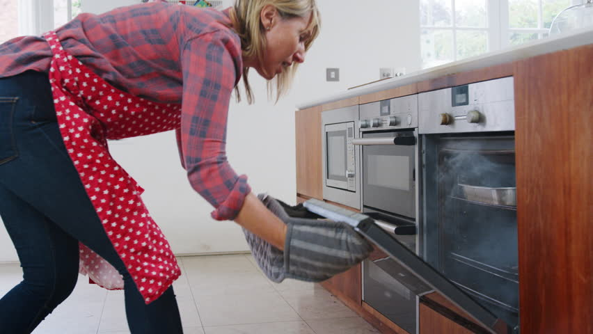 Mature Woman In Kitchen Takes Burning Meal Out Of Oven