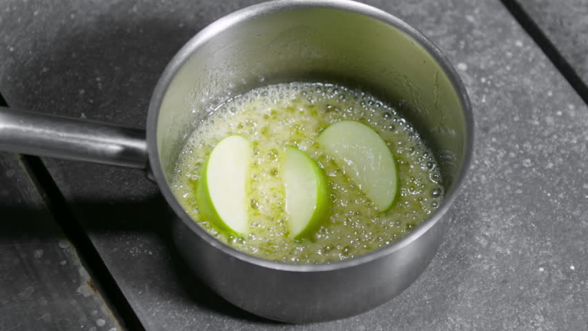 Zoom in shot of green apple slices sauteing with butter in saucepan standing on induction cooktop | Shutterstock HD Video #1009353827