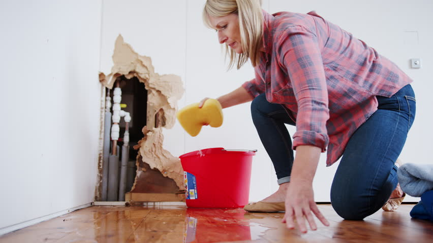 Mature Woman At Home Mopping Up Water From Leaking Pipe