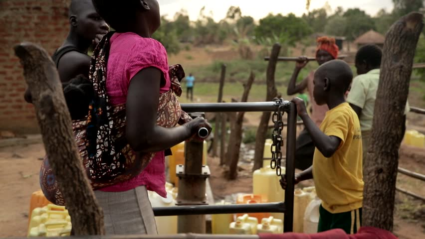 UGANDA, GULU - 15 February 2017: African children filling up a plastic container at a water well in Rural Uganda, Africa