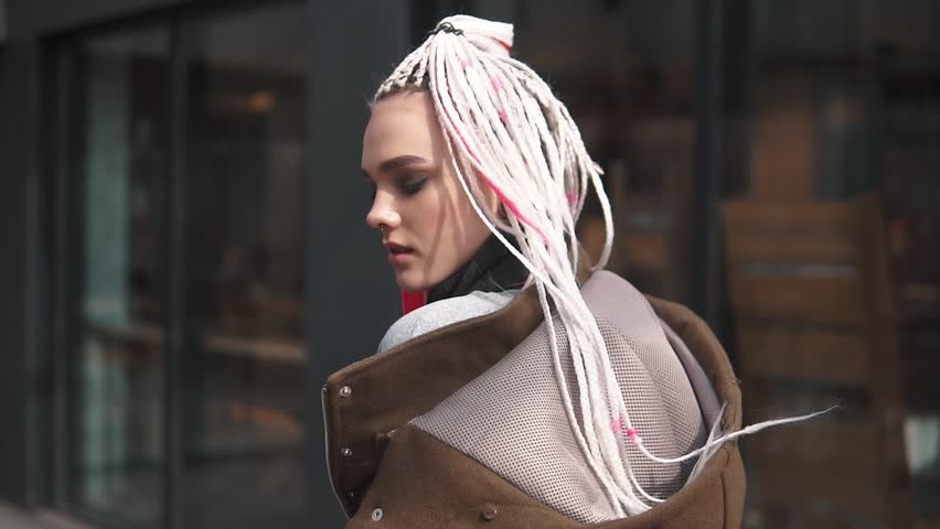 Girl with an unusual appearance on the background of urban architecture. teenager with dreadlocks and piercing. a modern youth culture. back view. slow motion | Shutterstock HD Video #1009367261