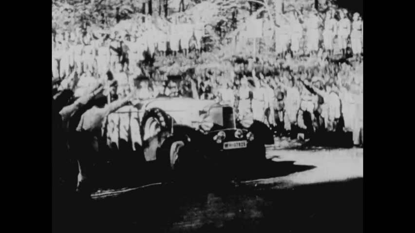 CIRCA 1943 - Adolf Hitler is driven in a military parade and warplanes and tanks are shown in Nazi Germany.