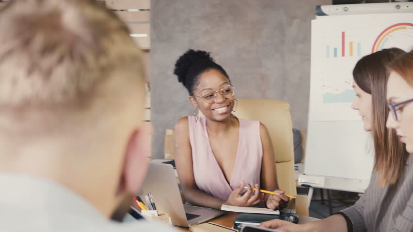 Multiethnic team tell jokes and laugh at meeting. Happy smiling creative millennial office employees generating ideas 4K #1009383386