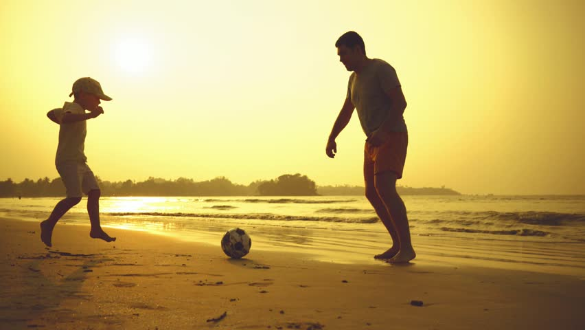 Father and son playing together with ball in football on the beach under sunset background #1009405802