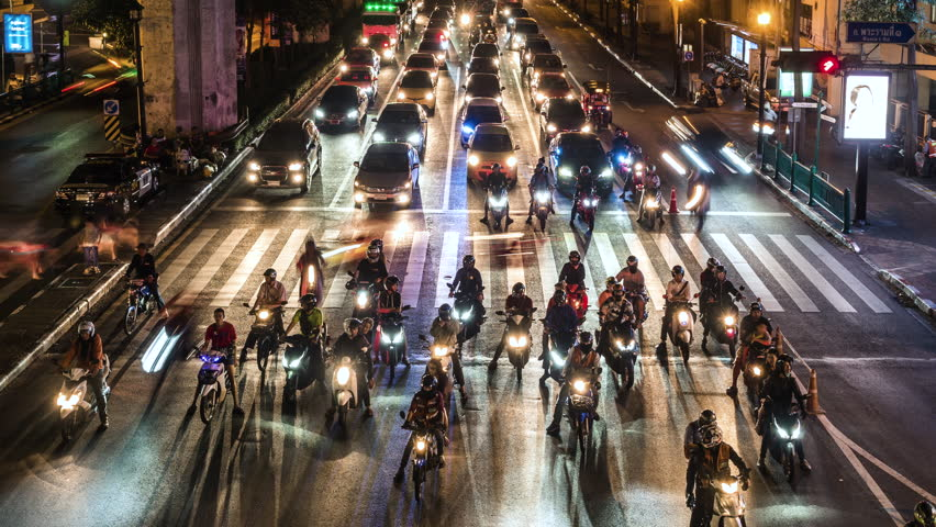 Timelapse view of night traffic at busy intersection in Bangkok, Thailand. Motorcycles, scooters and mopeds are a popular method of transportation in Thailand and many other Asian countries.